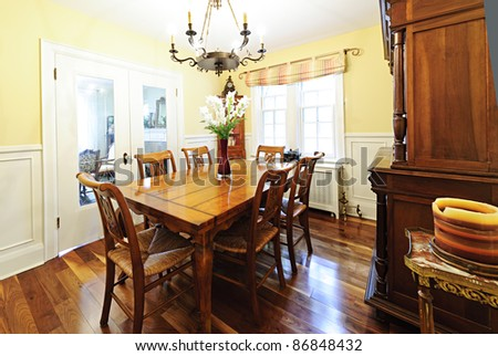 Dining room interior with wooden table and chairs in house - stock photo