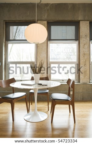 Dining room table and chairs in a modern loft setting. Vertical shot. - stock photo