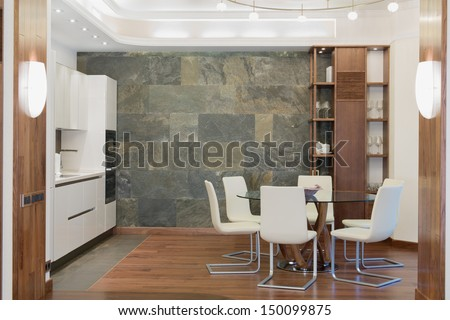 Dining room with a round glass table in the middle, white chairs and a cupboard - stock photo