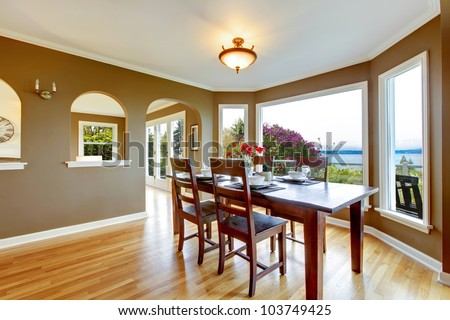 Dining room with brown walls and wood table with water view. - stock photo