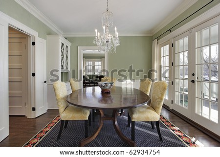 Dining room with green walls and door to deck - stock photo