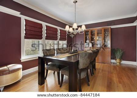 Dining room with maroon walls and three windows - stock photo