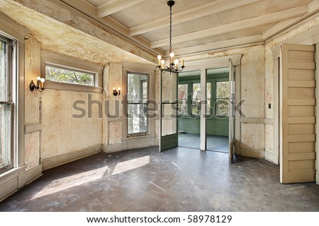 Dining room with peeling paint in old abandoned home - stock photo