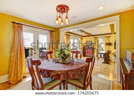 Dining room with rustic table set overlooking living room. Walkout deck