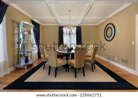 Dining room with tan walls and blue drapes - stock photo