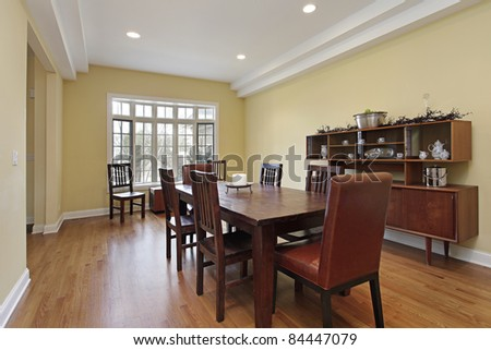 Dining room with tiered ceiling and wood buffet - stock photo