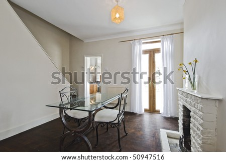 dining room with vintage glass top dining table and fireplace - stock photo