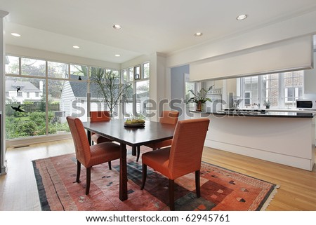 Dining room with wall of windows and orange chairs - stock photo