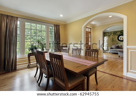 Dining room with yellow walls and foyer view - stock photo