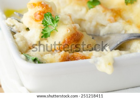 Dining scene. Close up of a dish of baked  golden cauliflower cheese with fork inserted.  Scattered with fresh parsley leaves and resting on a white cloth. - stock photo