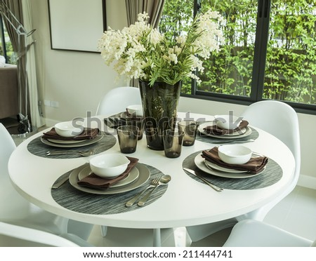 dining table and artificial flower in modern dining room - stock photo
