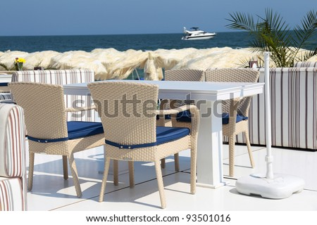 Dining table and chairs on the beach on a summer day