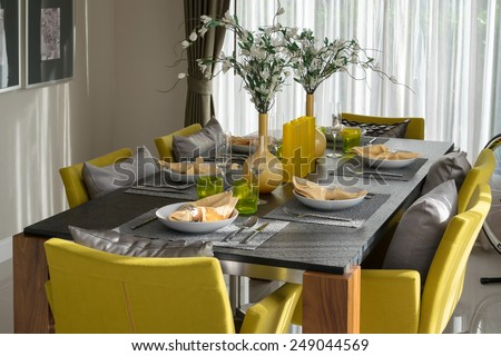 dining table and comfortable yellow chairs in modern home with elegant table setting - stock photo