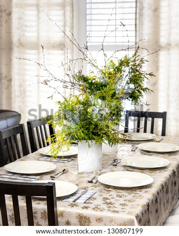 Dining table decorated for Christmas with eight place settings and evergreen centerpiece - stock photo