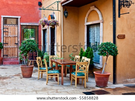 Dining table in front of the italian style buildings - stock photo