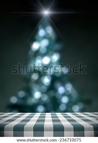 Dining table on blue lit christmas tree bokeh with star - stock photo
