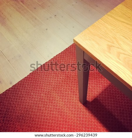 Dining table on red rug. Wooden floor background. - stock photo