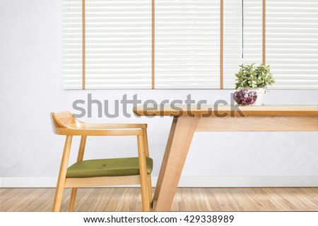 Dining table set with chair in the cozy dining room. wood table, wood chair, dining room, minimalist, empty table, white blinds, laminate floor, close up, furniture, plant pot and white wall - stock photo