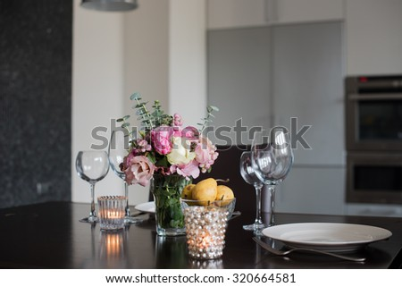 Dining table set with flowers, candles and glasses in the interior of modern kitchen