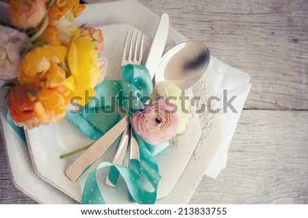 Dining table setting with buttercup flowers - stock photo