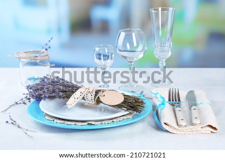Dining table setting with lavender flowers on table, on bright background - stock photo