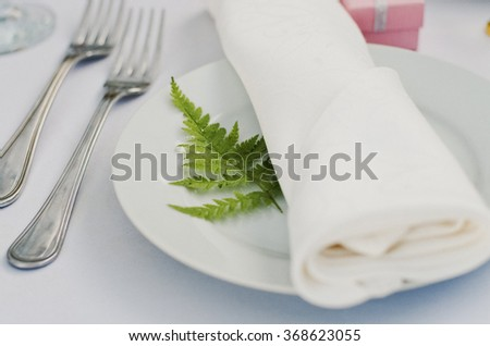Dining table setting with leaf of fern.