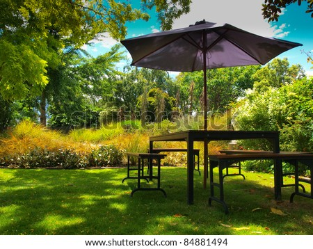 dining table with chairs and parasol in the shade in a lush garden - stock photo