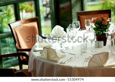 Dining table with glasses and silverware - stock photo