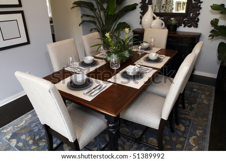 Dining table with modern tableware and decor.