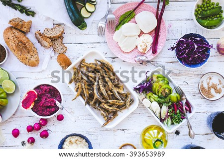 Dinner and seafood background. Veggies salads and dip with fried sardines, marinated cucumber and sandwich bread baguette from above on kitchen white wooden table. Rustic style. - stock photo