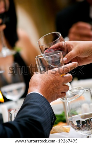Dinner at the restaurant. Men make a speech and invited to drink. - stock photo