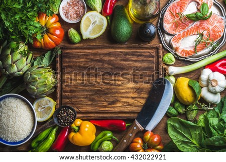Dinner cooking ingredients. Raw uncooked salmon fish steaks with vegetables, rice, herbs, spices and wine , rustic wooden chopping board in center, top view, copy space - stock photo
