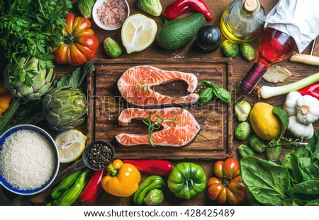 Dinner cooking ingredients. Raw uncooked salmon fish with vegetables, rice, herbs, spices and wine on chopping board over rustic wooden background, top view