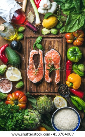 Dinner cooking ingredients. Two pieces of raw uncooked salmon fish with fresh vegetables, rice, herbs, lemon, spices and bottle of rose wine over rustic wooden board, top view, vertical composition - stock photo