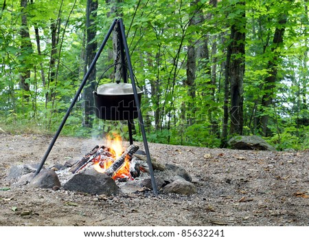 Dinner cooking on an open fire at the cottage - stock photo