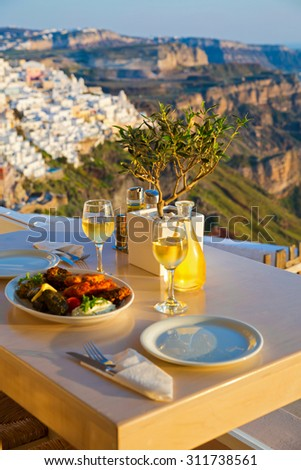 Dinner for two on a sunset background.Greece, Santorini, restaurant on the beach, above the volcano