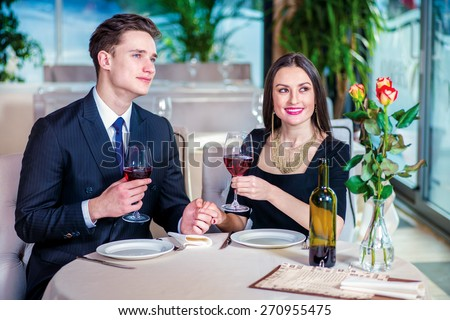 Dinner for two. Romantic dinner in the restaurant. Young loving couple visits a restaurant and raised their glasses of wine and look out the window until the guy holding the hand of a woman - stock photo