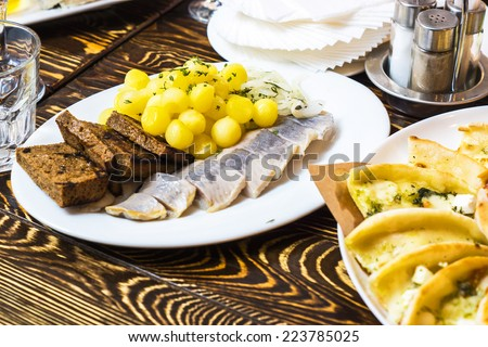 Dinner in russian restaurant - small fried potato dusted with greens and salted herring fish with bread toasted on a white plate on a brown wooden table  - stock photo