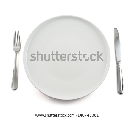 Dinner is served composition: table knife and fork next to the ceramic empty copyspace plate dish isolated over white background, top view
