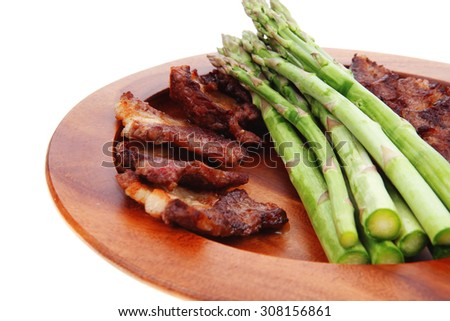 dinner of hot grilled beef meat ribs served with asparagus on wooden plate isolated on white background - stock photo