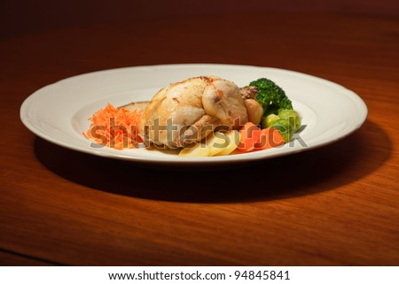Dinner of vegetables and chicken on a plate and wooden table