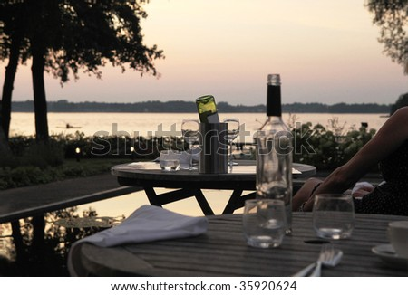 dinner on an outdoor terrace with sunset on a lake and empty bottles of wine - stock photo