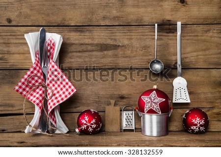 Dinner on christmas eve. Old wooden background with red white checked cutlery and dishes for decoration. - stock photo