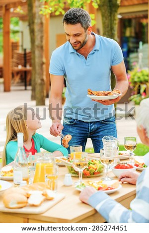 Dinner on fresh air. Young man putting grilled chicken to the plates while his family sitting at the dining table - stock photo