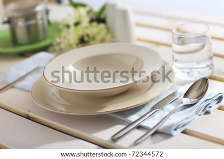 Dinner Place Setting On A Garden Table with Silver Spoon And Knife, Blue Napkin And Plates - stock photo