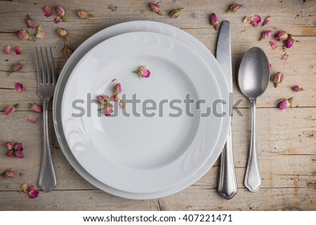 Dinner place setting - two plates of white porcelain, fork, spoon and knife on white, old, wooden table - stock photo
