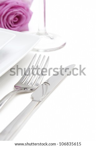 Dinner place setting. White china plates with fork, knife, glass and pink rose - stock photo