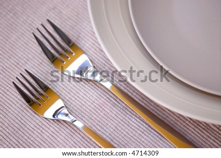 Dinner place setting with plates and cutlery shallow dof - stock photo