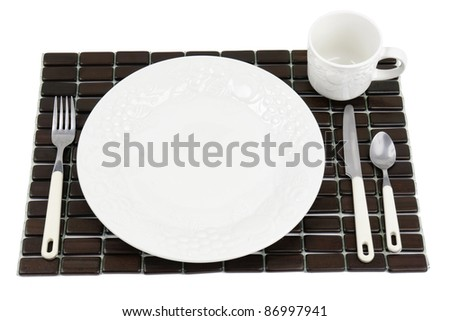 Dinner plate, white textured China with grapes and tomatoes design over a dark wood place mat. - stock photo