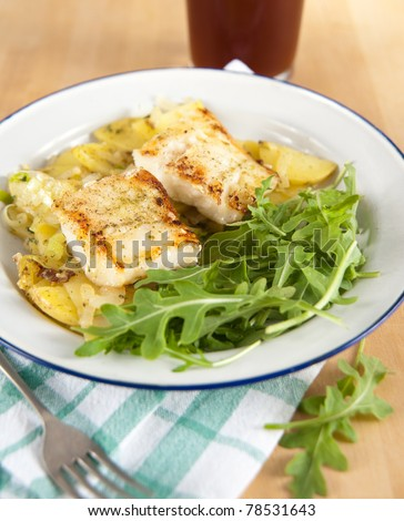 Dinner Plate with Fried Potatoes and Grilled Cod with Side of Fresh baby Arugula - stock photo